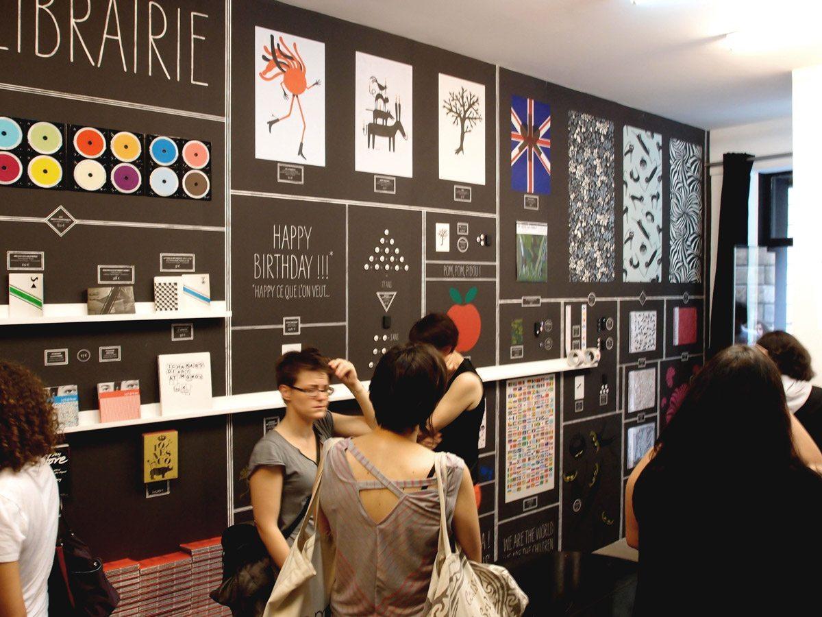 Exposition à la galerie SometimesStudio, Ichetkar présente dans une salle recouverte de papier peint tous ces produits accrochés au mur. Scénographie IchetKar
