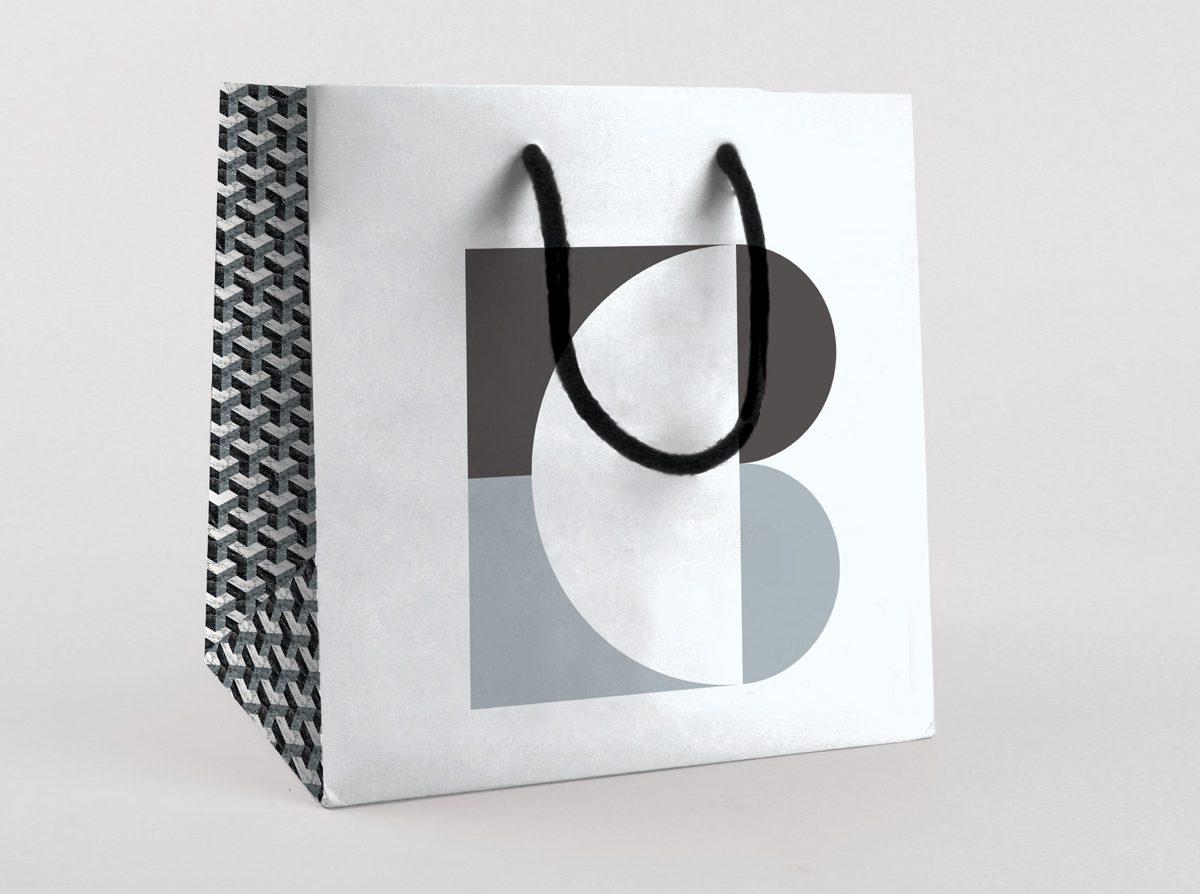 Sac en papier du marbrier Blanc Carrare. Couleurs noir, blanc et gris, inspirés du marbre et de la lave. Design Ich&Kar.