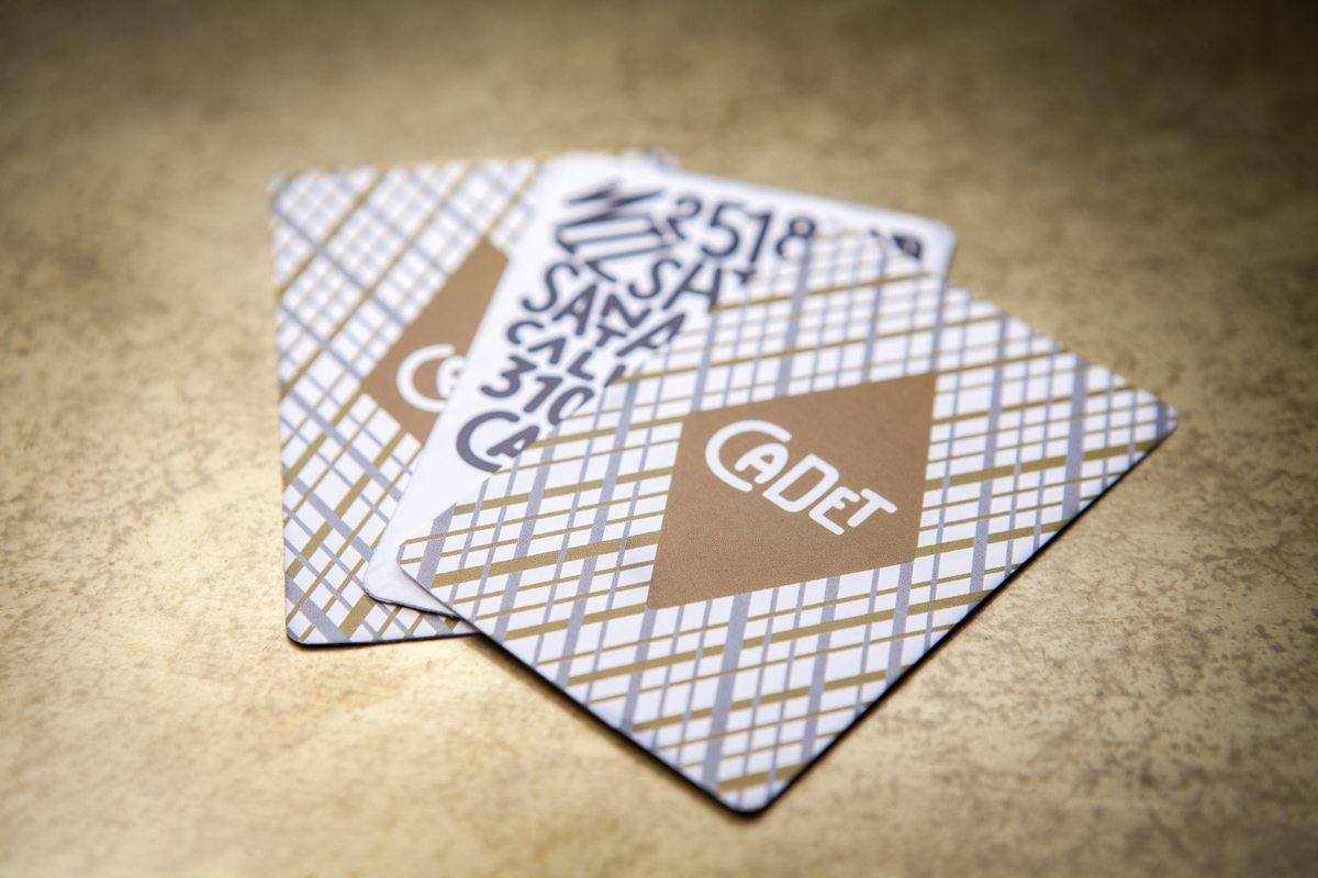 Cartes de visite du restaurant Cadet à Los Angeles. Des cartes qui ressemblent à des miniatures de cartes à jouer, imprimée d'or, de bronze et d'argent, les couleurs moirent élégamment coté pile, tandis que la typographie noire en relief danse coté face… Design Ich&Kar