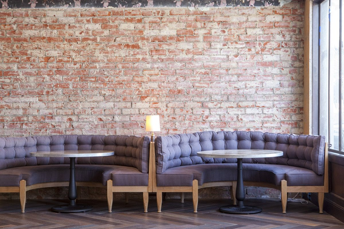 Cadet restaurant booth brick wall. Intérieur du restaurant Cadet, mur de briques. canapés mauves et tables.