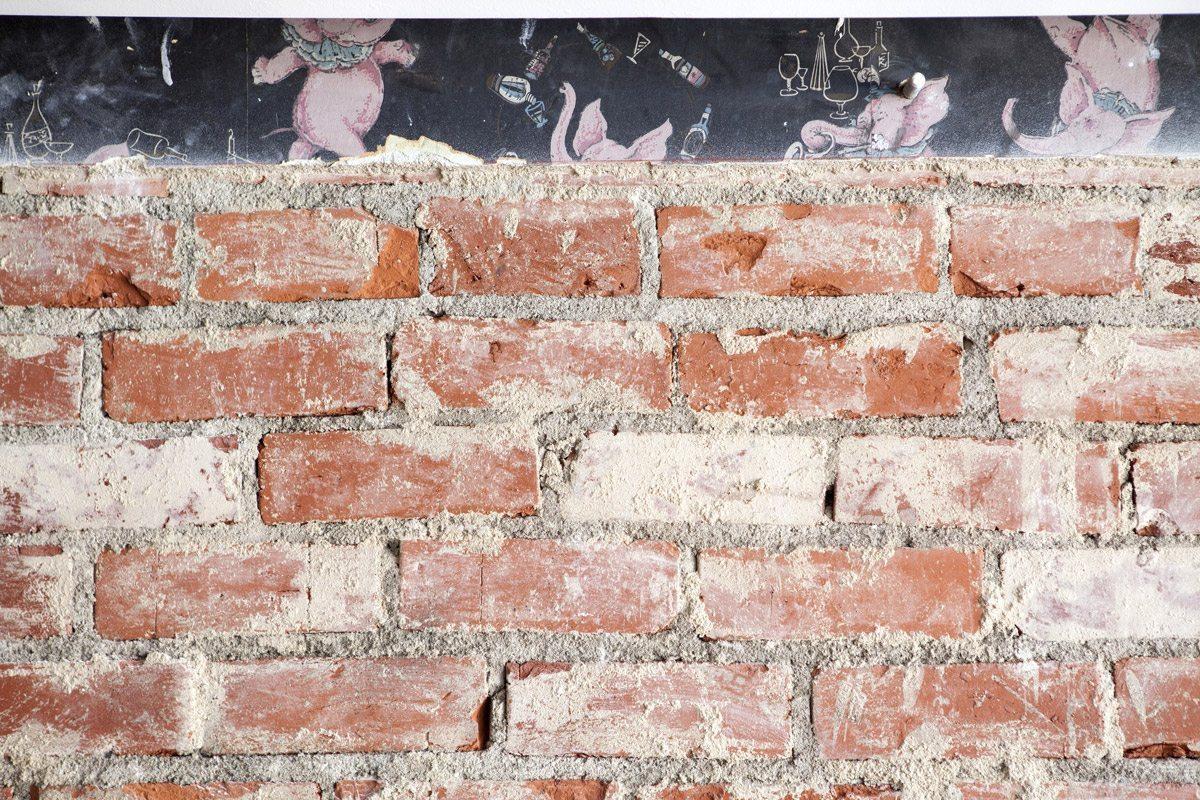 Vue d'un mur de l'intérieur du restaurant cadet à Los Angeles. Mur de briques, avec les traces d'un ancien papier peint vintage illustrant des petits éléphants. Bricks and éléphant wallpaper at Cadet restaurant, at Los Angeles.
