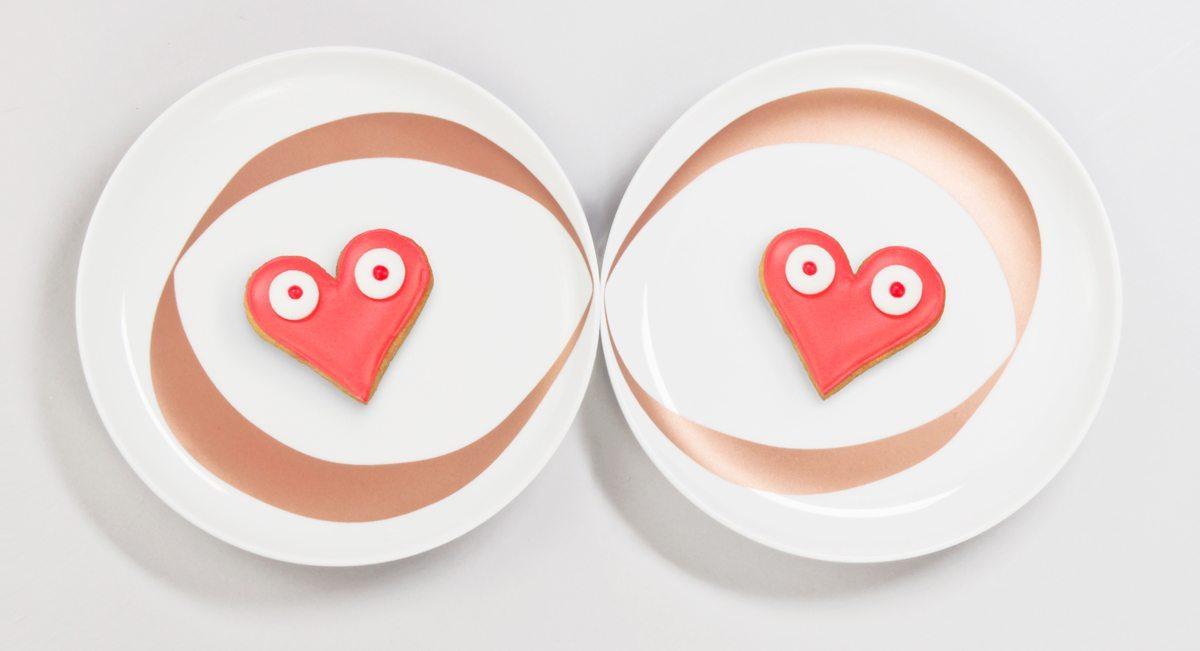 Assiettes infini : Chaque assiette blanche est ornée d'un anneaux cuivré. Mises côte à côte, cela donne un dessin de Ruban de Moebuis. Symbole de l'amour à l'infini. Ici, sont posés sur les assiettes deux gâteaux rouges en forme de coeur, réalisés par la pâtisserie Bogato. Assiettes créees pour le DesignerBox 21 par Ich&Kar
