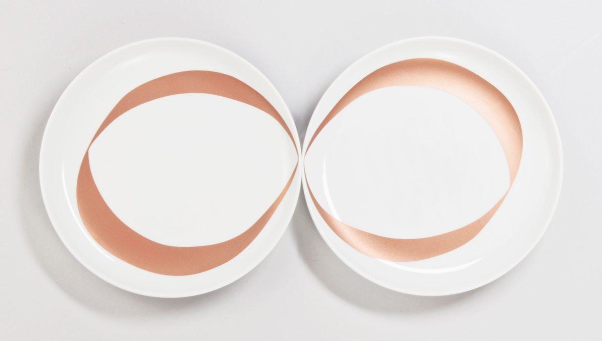 Assiettes infini : Chaque assiette blanche est ornée d'un anneaux cuivré. Mises côte à côte, cela donne un dessin de Ruban de Moebuis. Symbole de l'amour à l'infini. Assiettes à desserts pour amoureux. Produits crées pour la DesignerBox 21 par Ich&Kar