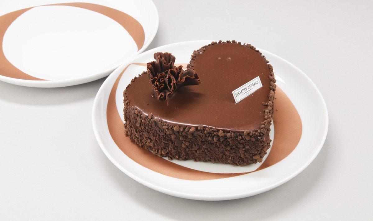 Assiettes infini : Deux assiettes blanches ornées d'anneaux cuivrés. Assiettes à desserts pour amoureux. Sur une des assiette, est posé un gâteau en forme de coeur, un Mussipontain du pâtissier Sebastien Gaudard. Assiettes crées pour la DesignerBox 21 par Ich&Kar