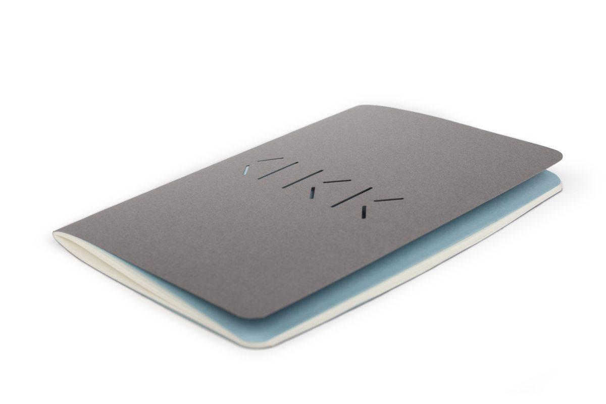 Carnet gris d'Annabel Karim Kassar, couverture perforée du logo AKK, moderne et minimaliste
