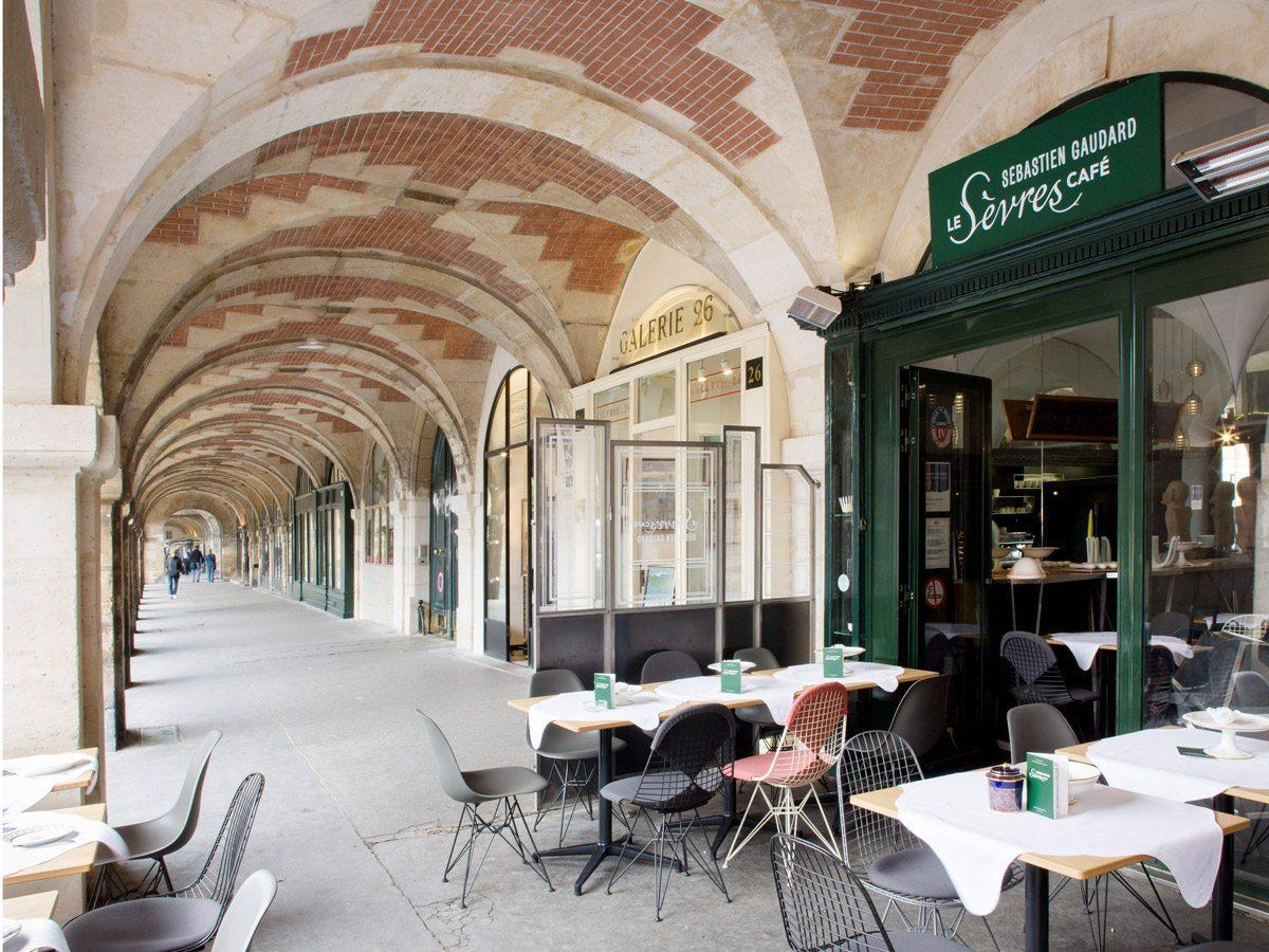 Terrasse et façade du Sèvres Café par Sébastien Gaudard, dans une arcade de la Place des Vosges à Paris