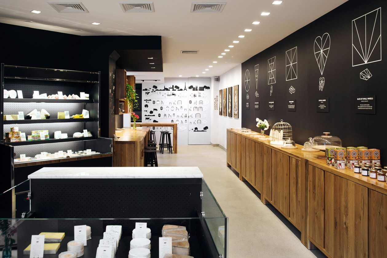 photo of Interior design of french cheese board by Pascal Perich with oak furniture blacks fridges filled with french cheeses