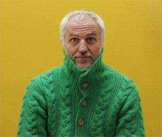 mourad mazouz avec un pull vert sur fond jaune