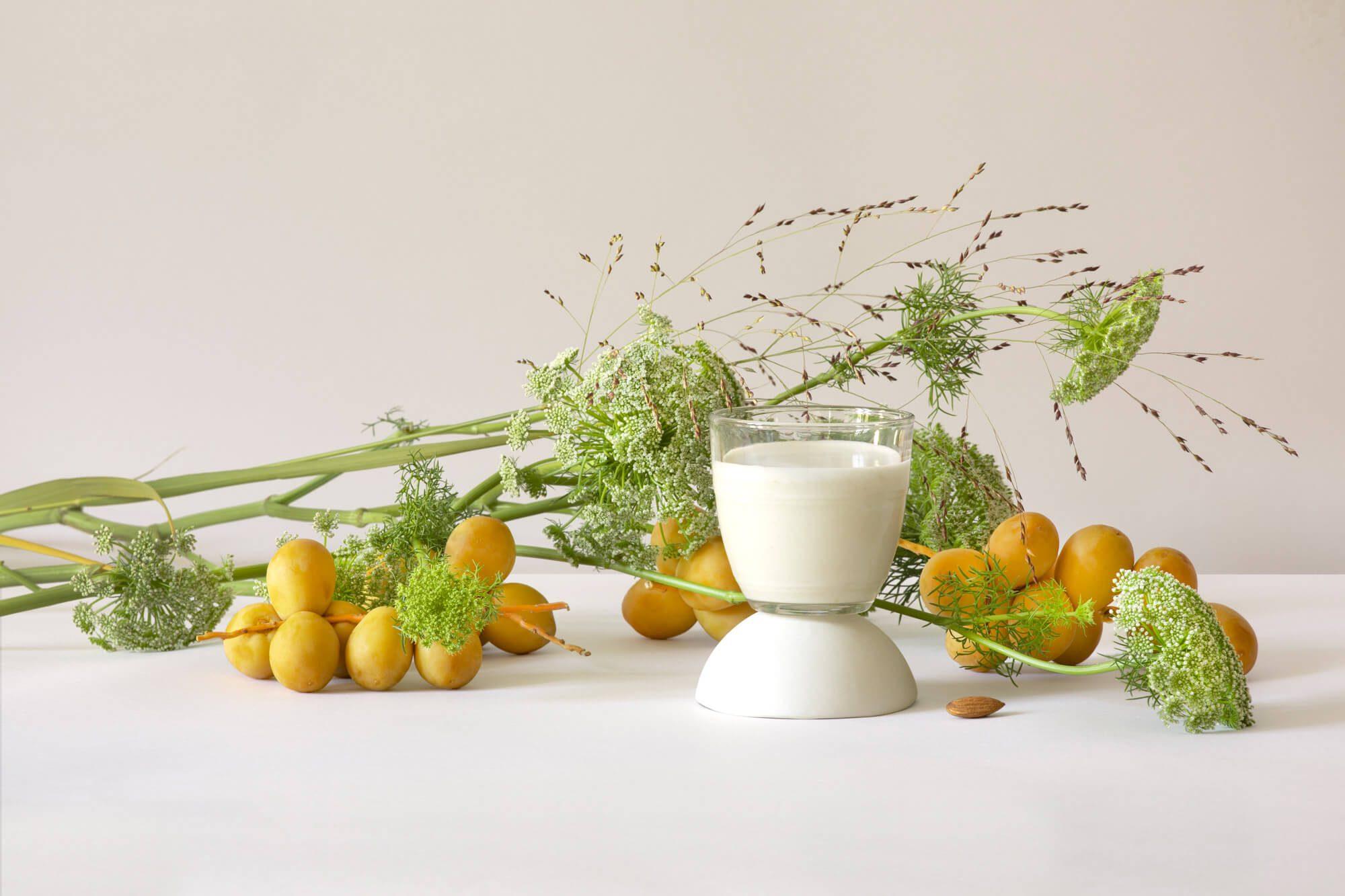 une nature morte minimaliste sur fond clair avec dattes fraiches laits infusés et plantes, le studio IchetKar fait équipe avec la photographe Virginie Perocheau