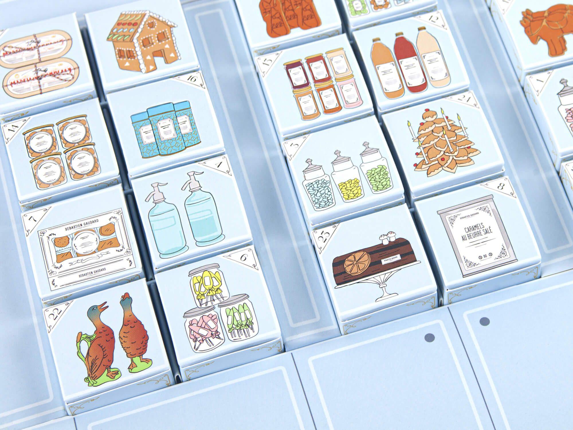 Gors plan sur le calendrier de l'avent de SG, une maquette des étagères de la pâtisserie des martyrs remplie de 24 illustrations de noël par les graphistes Ich&Kar
